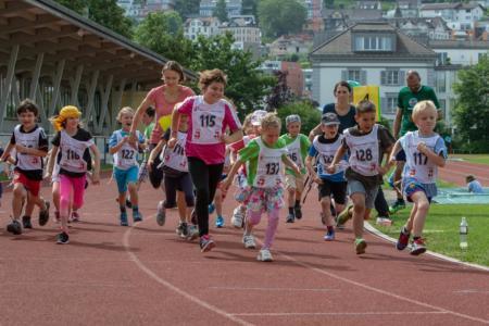 Schüler Basisstufe beim Laufstart mit Startnummern auf Laufbahn