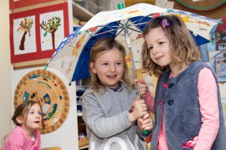 Zwei Schülerinnen unter Regenschirm